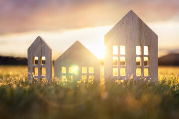 Ecological wood  model house in empty field at sunset