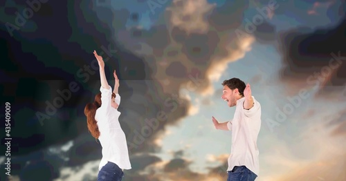 Composition of happy couple celebrating with arms outstretched, over cloudy sky