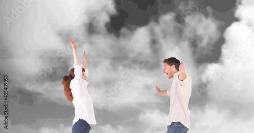 Composition of happy couple celebrating with arms outstretched over black and white cloudy sky