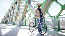 Young Business Man Commuter With Bicycle Going To Work Outdoors On Bridge In City, Coronavirus Concept.