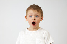 A Small Boy With Blue Eyes Opened His Mouth In Surprise Against A White Background. The Emotion Of Surprise On The Child's Face