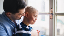 Father With Happy Down Syndrome Son Indoors At Home, Looking Through Window.