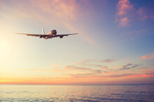 Airplane Flying Over Tropical Beach With Smooth Wave And Sunset Sky Abstract Background.
