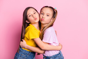 Photo of optimistic brunette blond girls hug wear yellow pink t-shirt isolated on pink color background