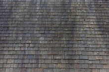 Old Dark Brown Stone Tiles Covered With Moss And Rust Stain On Brick Roof, Shingles Texture, Abstract Geometric Pattern Background, Details Of Roof Top Material.