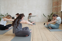 Girls In Activewear Stretching Arms In Front Of Themselves During Yoga Practice