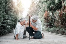 Asian Senior Woman Falling Down On Lying Floor At Home After Stumbled At The Doorstep And Crying In Pain And Her Husband Came To Help Support. Concept Of Old Elderly Insurance And Health Care