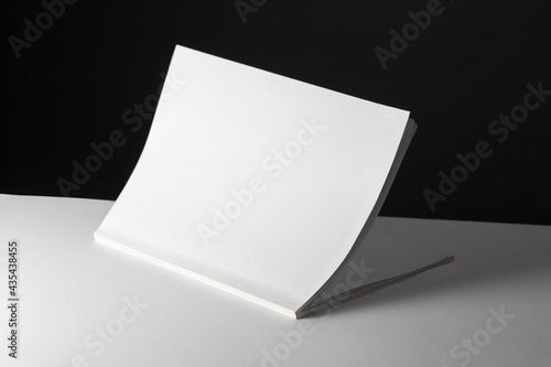 Composition of half opened book with blank pages on black and white background