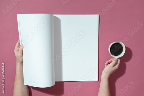 Composition of caucasian woman holding opened book with blank pages and coffee on pink