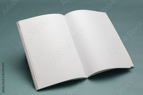 Composition of opened book with blank pages on blue background
