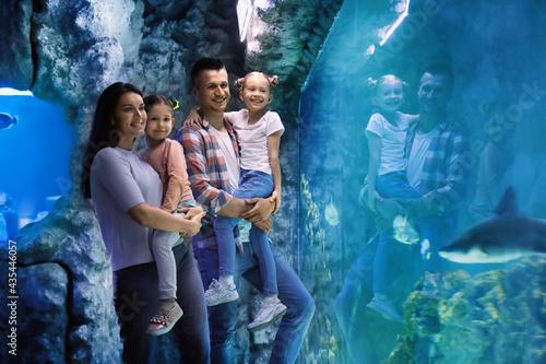 Happy family near aquarium in oceanarium. Spending time together Fotobehang
