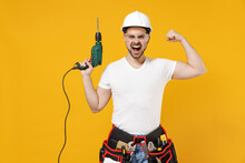 Young Fun Employee Handyman Man In Protective Helmet Glasses Hold Electric Drill Do Winner Gesture Isolated On Yellow Background. Instruments Accessories Renovation Apartment Room Repair Home Concept.