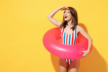Happy Fun Young Sexy Woman Slim Body Wear Striped Red Blue One-piece Swimsuit Hold Pink Inflatable Ring Isolated On Vivid Yellow Color Background Studio Summer Hotel Pool Sea Rest Sun Tan Concept