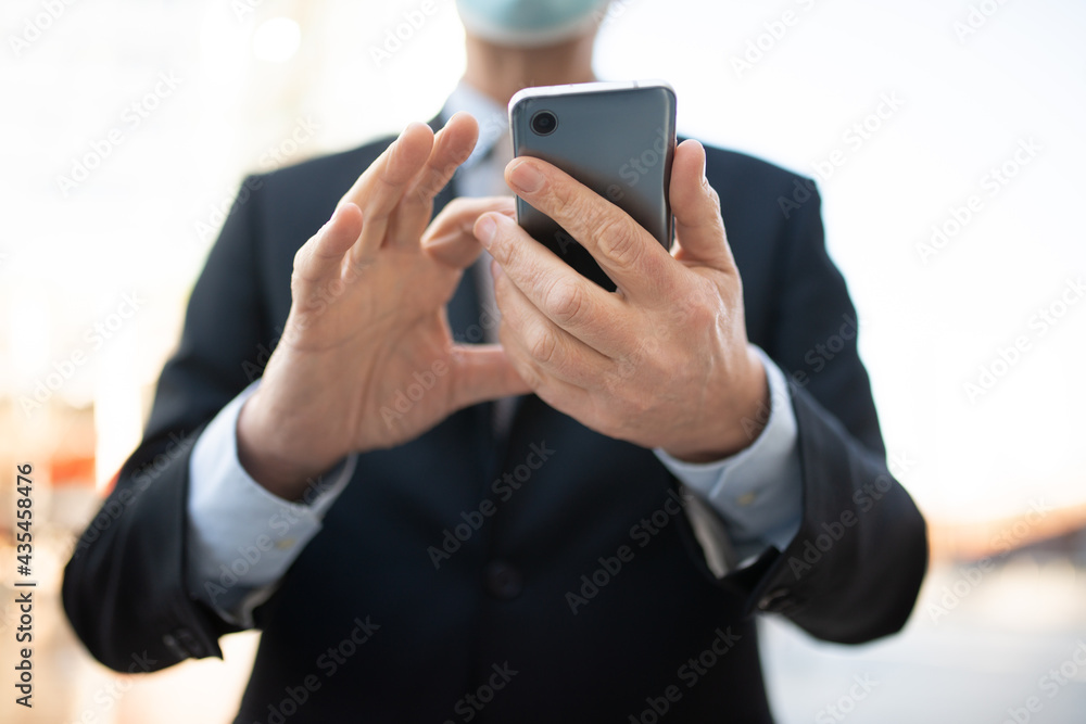 Masked businessman using his smartphone outdoor, covid and coronavirus concept