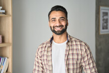 Headshot Portrait Of Attractive Confident Indian Hispanic Man With Toothy Smile Looking At Camera At Modern Living Room. Latin Businessman Posing In Casual Stylish Look At Home Office.