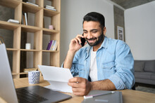Young Happy Smiling Adult Indian Hispanic Businessman Talking On Mobile Cellphone Arranging Meeting With Employee Reading Paper CV Sitting At Desk At Home Office. Remote Recruitment Work Concept.