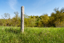 A Old, Weathered Fence Post Stands Alone In A Field