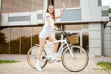 Young Woman Travels To The City By Bicycle. Rent And Hire Transport For The Day. Happy Girl Rides A Bike. Sports Lifestyle Waving Hand