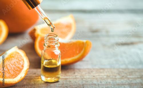Fotografiet Orange essential oil in a small bottle. Selective focus.