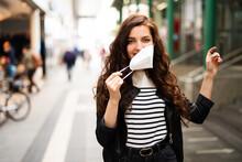 Junge Frau Zieht Freudig Ihre FFP2 Maske Aus, Ende Der Maskenpflicht