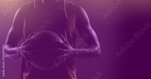 Composition of fit male basketball player holding ball with copy space on purple background