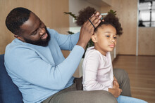 African American Father Brushing Making Hairstyle For His Young Daughter
