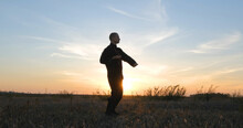 Silhouette Of Young Male Kung Fu Fighter Practising Alone In The Fields During Sunset