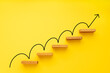 Leinwandbild Motiv Rising arrow on staircase on yellow background. Growth, increasing business, success process concept