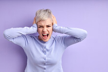 Inner Pain. Devastated Young Caucasian Woman Closing Ears With Hands, Screaming, On Purple Studio Wall With Empty Space For Your Promotional Content. Desperate Female With Short Hair