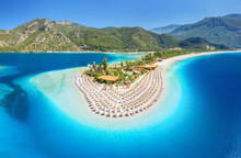 Aerial View Of Sea Bay, Sandy Beach With Umbrellas, Trees, Mountain At Sunny Day In Summer. Blue Lagoon In Oludeniz, Turkey. Tropical Landscape With Island, White Sandy Bank, Blue Water. Top View