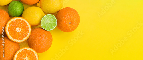 Fotografiet orange, lemon and lime on a yellow background