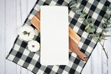 Kitchen Tea Towel Dish Cloth Mockup. On-trend Farmhouse Aesthetic Flatlay Svg Craft Product Mock Up With Black Plaid Table Cloth And White Pumpkins On A White Wood Background. Negative Copy Space.
