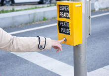 """Woman's Finger Pressing The Pedestrian Button Of A Traffic Light. The Words That Appear Mean: """"wait Pedestrian"""", """"press Pedestrian""""."""