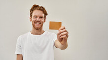 Young Redhead Man Holds Credit Card In Front Of Him
