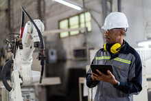 African American Male Engineer Worker Using Digital Tablet Control Automatic Robotic Hand Machine In Factory. Black Male Technician Worker Working With Control Automatic Robot Arm System Welding