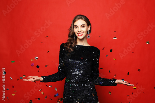 Fotografiet Holiday and party concept: beautiful young woman wearing evening dress standing