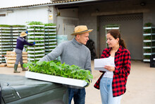 Young Girl Farmer Buying Trays Of Seedlings From European Man At Agricultural Warehouse