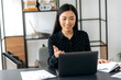 Charismatic successful confident Asian business lady, freelancer, manager, using laptop, talking on video conference with client or colleague, discussing business project, gesturing with hand, smiling