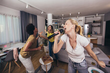 Young Womanl Singing Into Microphone At Home Party Having Fun. Bachelorette Party, Karaoke, Music Concert And Holidays Concept