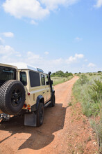 Cream Yellow Land Drover Defender In Front Of Dirt Road