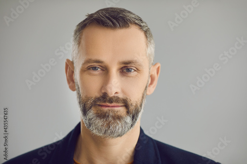 Papel de parede Portrait of confident attractive senior European business man looking at camera with friendly face expression on gray studio background