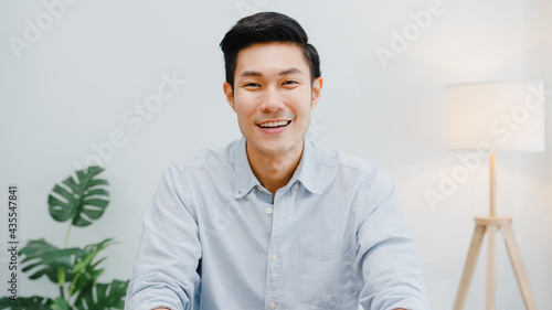 Portrait of successful handsome executive businessman smart casual wear looking at camera and smiling, happy in modern office workplace. Young Asia guy talk to colleague in video call meeting at home.