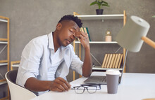 Tired Guy Rubs Nose Bridge Sitting At Study Desk. Man Suffers From Vision Problem Or Computer Eye Strain. Upset Male Student Exhausted After Work On Laptop And Endless Online Distance Learning Classes