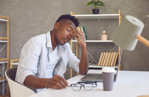 Stampa su Tela Tired guy rubs nose bridge sitting at study desk
