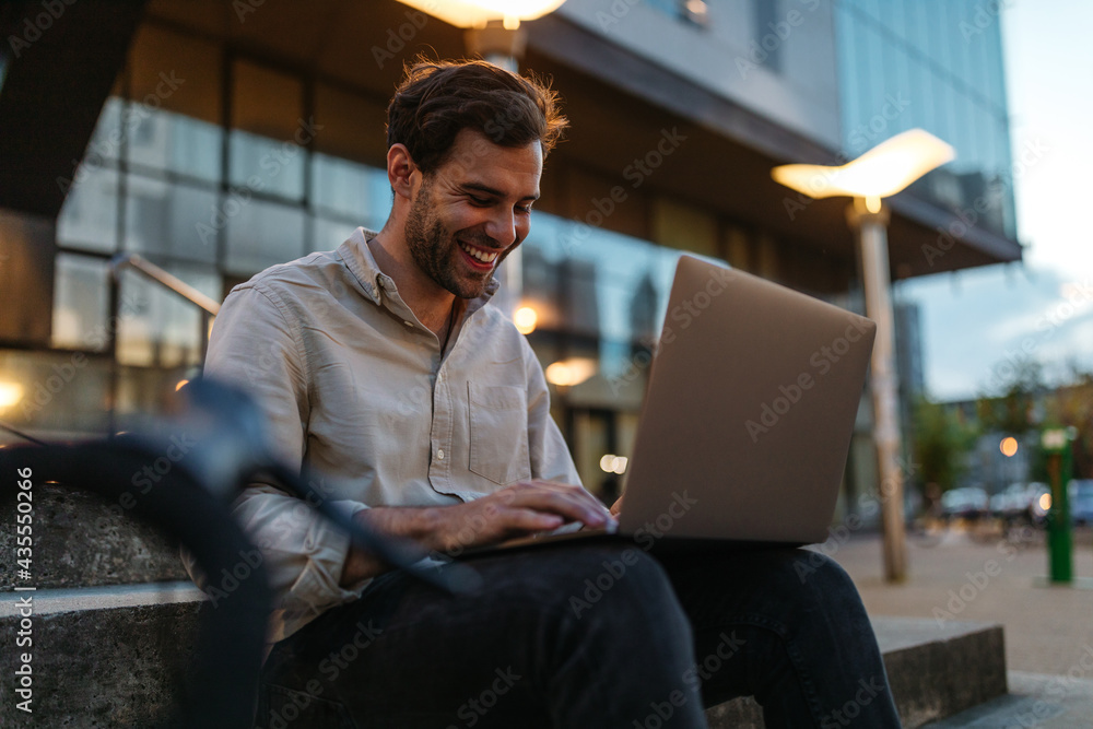 Businessman sitting on the bench with laptop.