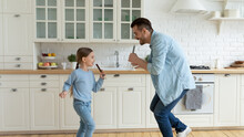 Overjoyed Young Caucasian Father Have Fun Sing In Kitchen Appliances With Small Daughter. Happy Dad Play And Dance At Home With Little Teen Girl Child On Leisure Family Weekend. Parenthood Concept.