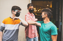 Young Friends Bump Their Elbows To Greet In Time Covid-19. They Use The Mask To Defend Themselves From The Coronavirus. Concept Of Social Distance And Friendship.