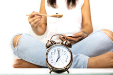 Selective Focus Of Alarm Clock  Which  Young Woman Background, She Is Intermittent Fasting Eating With Yogurt As Granola And Healthy Food Concept Image