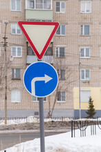 Traffic Signs Mean Give Way And Turn Right Only At The Edge Of The Road. Against The Background Of A Road And A Residential Building. It's Winter In The City, White Snow Lies On The Street.