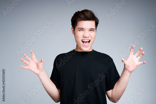 Canvas Funny asian guy in black t-shirt and short hair fooling around and acts like a b